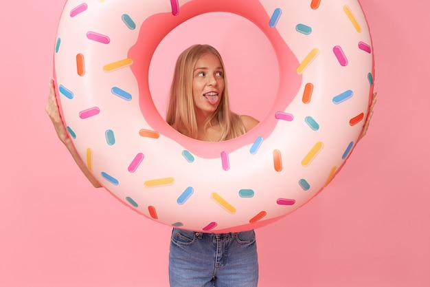 Изолированные портрет модной молодой блондинки носить рваные джинсы, весело во время летних каникул, держа розовое плавательное кольцо