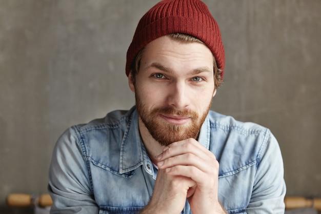 コンクリートの壁に座っているハンサムな若いひげを生やしたヨーロッパ男性の孤立した肖像画