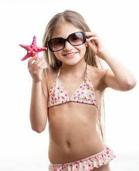 Изолированный портрет счастливой улыбающейся девушки в солнцезащитных очках, позирующей с красной морской звездой