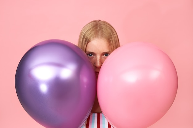 そばかすと2つの光沢のある金属製のヘリウム気球の後ろに身を隠しているピンクにポーズをとって顔のピアスと神秘的な若いブロンドの女性の孤立した肖像画
