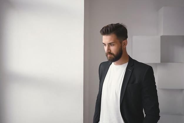 흰색 사무실 벽 배경에 대해 창가에 서있는 퍼지 수염과 머리가있는 잠겨있는 심각한 젊은 남성 직원의 고립 된 초상화, 작업 문제에 대해 생각하고 깊은 생각