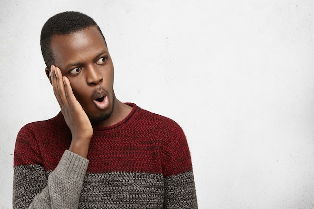 Изолированный портрет потрясенного молодого афроамериканского мужчины в вскользь свитере смотря в полном неверии, руке на щеке, удивленной с некоторыми удивительными новостями человеческие эмоции, чувства, отношение, реакция