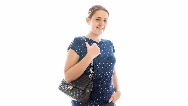 Изолированные портрет улыбается взрослая женщина с черной сумочкой, глядя в камеру.