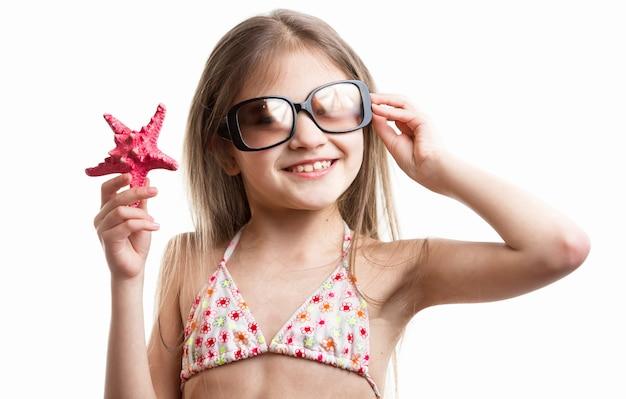 Изолированный портрет улыбающейся девушки брюнетки, позирующей с красной морской звездой