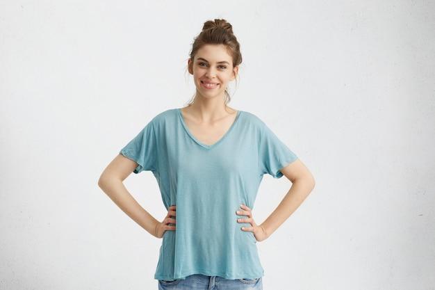 Изолированный портрет улыбающейся веселой женщины в негабаритном топе и джинсах, позирующей, держа руки на талии и смотрящей с широкой счастливой улыбкой, наслаждаясь приятным временем в помещении
