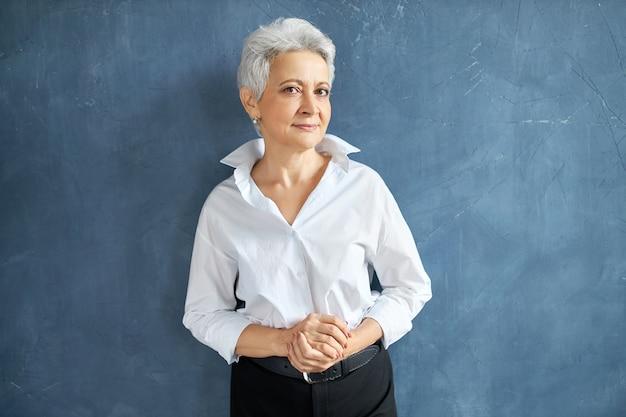 자신감이 자세로 서있는 짧은 회색 머리를 가진 세련된 경험이 풍부한 중년 여성 임원의 고립 된 초상화