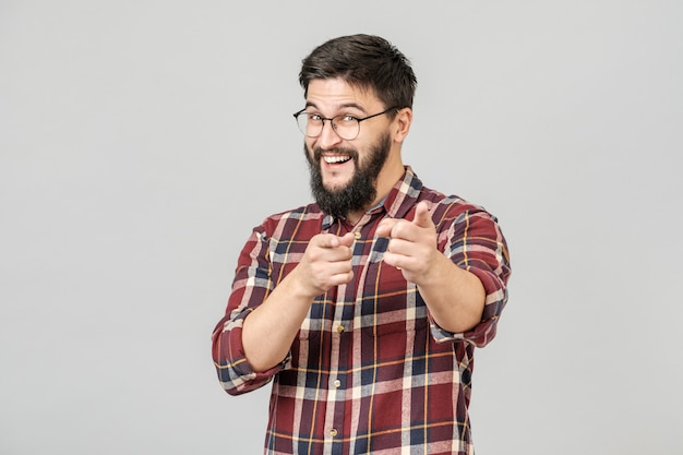 Изолированные портрет молодого человека, весело улыбаясь, указывая пальцем на камеру