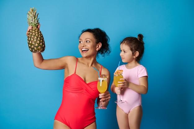 Изолированный портрет на синем фоне с красивой улыбающейся матерью и ее дочерью в купальниках, держащей стакан с тропическим соком и ананасом