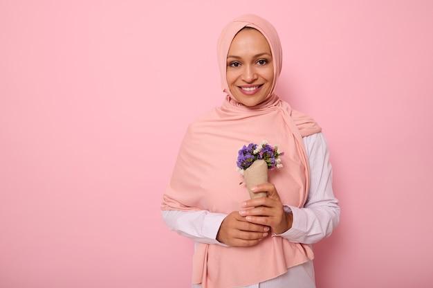 분홍색 히잡을 쓴 아름다운 이슬람 아랍 여성의 색색 배경에 고립된 초상화, 보라색 색조의 야생화 꽃다발을 들고 공예 종이에 싸여 이빨 미소로 카메라에 미소