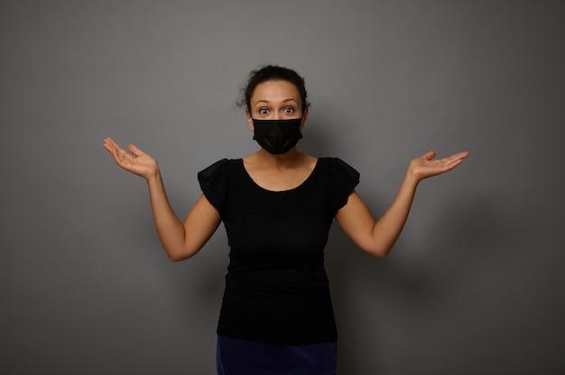 広告用の架空のコピースペースを保持し、手のひらを持ち上げて黒い保護医療マスクで驚いた女性の灰色の背景に孤立した肖像画。ブラックフライデーのコンセプト