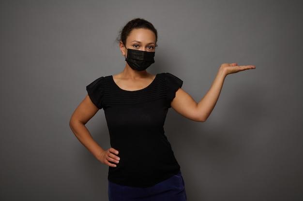 広告のための架空のコピースペースを保持しながら手のひらを上げる黒い保護医療マスクを身に着けている自信を持って穏やかな女性の灰色の背景に孤立した肖像画。ブラックフライデーのコンセプト