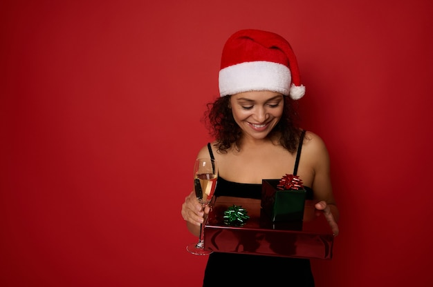 빨간 배경에 격리된 초상화는 산타 모자를 쓰고 스파클링 와인 한 잔을 들고 그녀의 손에 있는 선물 상자를 보고 있는 밝은 여성의 미소입니다. 복사 공간이 있는 크리스마스와 새해 개념