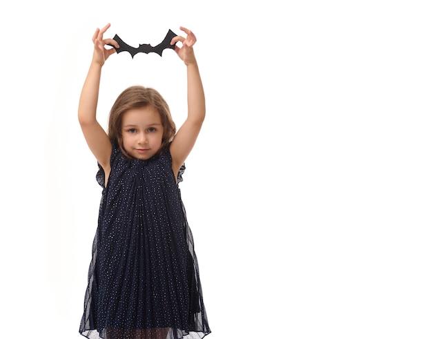 彼女の上げられた手でフェルトカットのバットを保持している4歳のかわいい女の子のコピースペースと白い背景の上の孤立した肖像画。ハッピーハロウィンのコンセプト、伝統的な季節のイベント