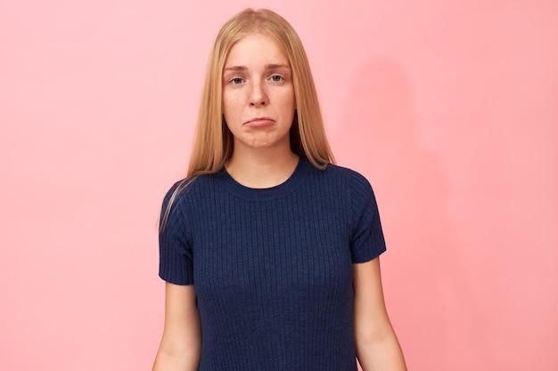 Isolato ritratto di bella bionda giovane donna in posa sul muro rosa copia spazio con espressione facciale infelice con angoli labbra tirato verso il basso