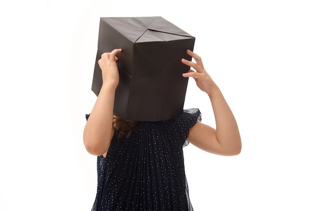 Isolated portrait of pretty girl having fun, putting a black shopping packet on her head, posing over white background, copy space . black friday concept