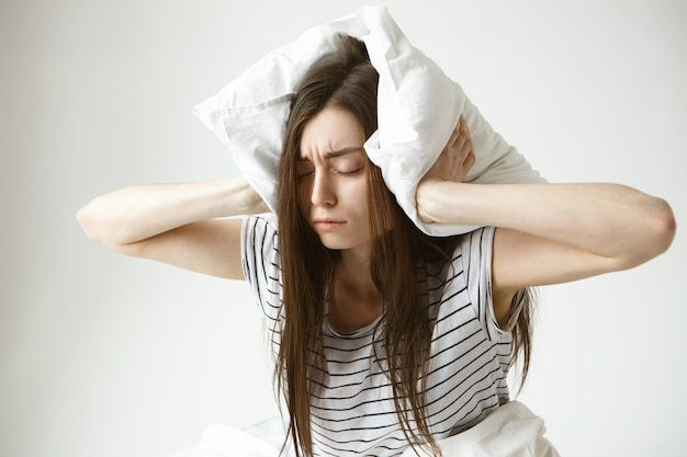 Isolated portrait of stressed young brunette woman wearing striped pajamas covering ears with white pillow feeling frustrated as she can't fall asleep at night because of her snoring husband