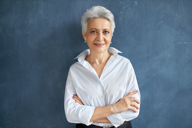 Isolated portrait of stylish successful 50 year old female broker in white shirt posing on blank wall