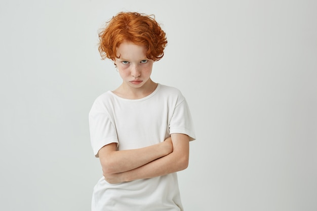 Isolated portrait of unhappy little kid with red curly hair and freckles being offended