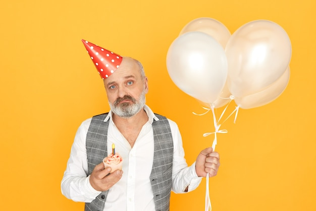Isolated portrait of unhappy unshaven male pensioner with cone hat on his bald head being depressed, getting old, holding balloons and cupcake