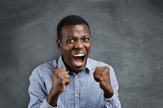 Isolated portrait of young angry african man in blue shirt clenching his fists, screaming with anger or rage, opening mouth widely.