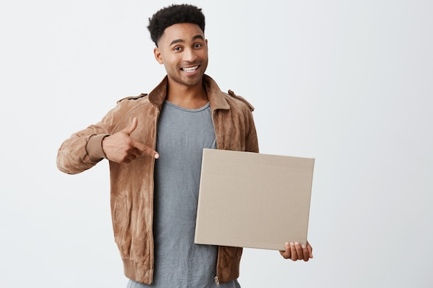 Isolated portrait of young black-skinned man with afro hairstyle in fashionable casual look holding carton board, pointing at it with hand, looking in camera with excited expression