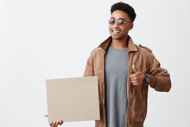Isolated portrait of young dark-skinned african male student with curly hair in casual trendy outfit and sunglasses holding paper board, showing thumb up, smiles brightly. positive emotions