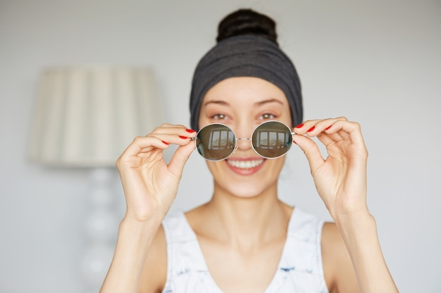 Isolated portrait of young female holding round shades that she just bought during shopping