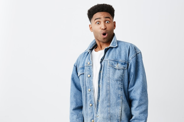Isolated portrait of young funny dark-skinned man surprised with afro hairstyle in casual white shirt under denim jacket with excited face expression