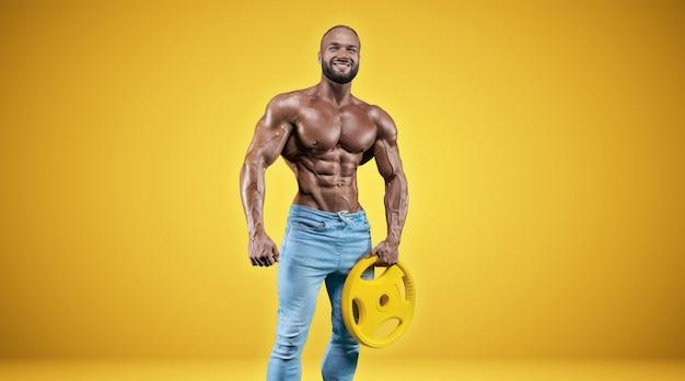 Изолированные профессиональный спортсмен на желтом фоне. концепция бодибилдинга. панорама. реклама тренажерного зала и спортивного питания. смешанная техника