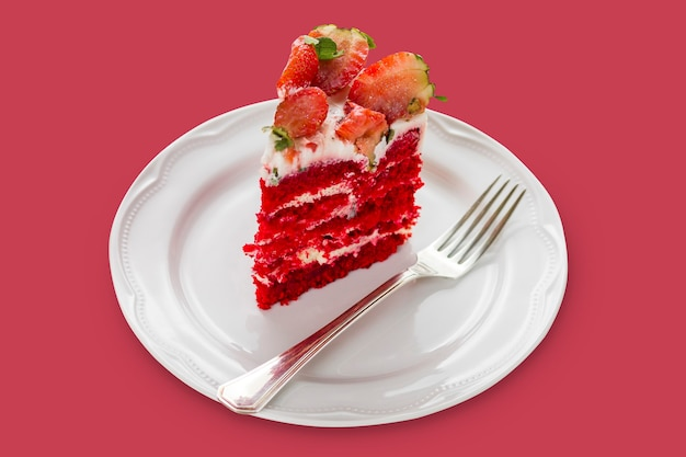 Изолированный красный бархатный торт на белой деревянной предпосылке. с клубникой