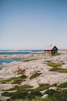 Isolated red wooden house on the shore near the ocean under the blue sky on a sunny day