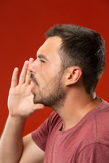 Isolated on red young casual man shouting