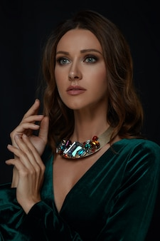 Isolated rich aristocratic makeup woman with brown curls hair in green neckline dress with jewelry necklace holds hands up and touch together and sensuality looks to side with wait on black background