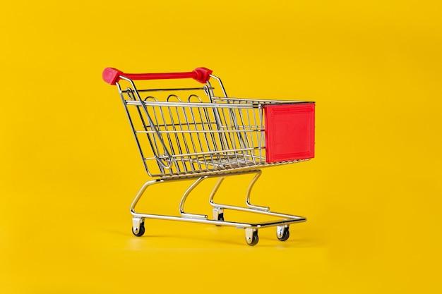 黄色の背景に孤立したショッピングカート。