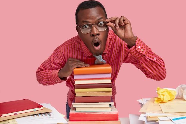 Colpo isolato di stupito giovane uomo di colore guarda scrupolosamente attraverso gli occhiali, si appoggia su una pila di libri, tiene la mano sul bordo degli occhiali