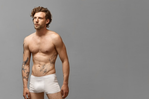 Colpo isolato di uomo atletico attraente con acconciatura alla moda e tatuaggi sul braccio e torso nudo che indossa solo boxer bianchi in posa al muro bianco con copyspace per la tua pubblicità