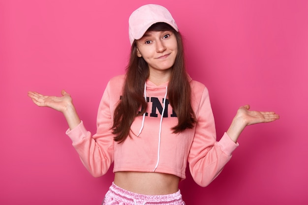 Isolated shot of attractive brunette pretty teenager, wears rose hoodie and cap