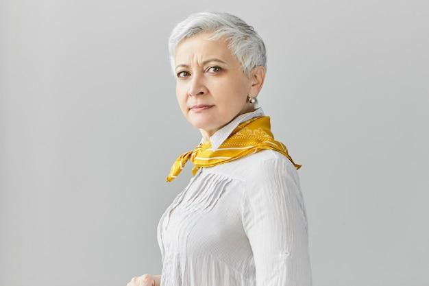 Colpo isolato di attraente fiduciosa donna di mezza età di 60 anni con i capelli grigi corti che farà una passeggiata, indossa una camicetta e sciarpa di seta, posa contro il muro vuoto