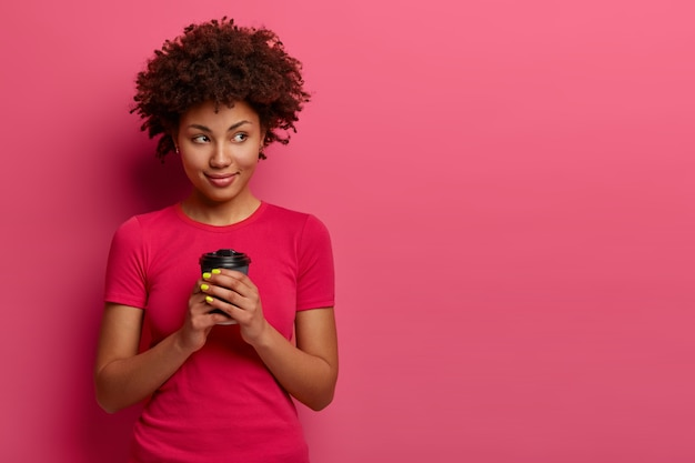 Isolated shot of attractive curly woman holds takeaway coffee, looks aside and thinks about something while drinking, enjoys spare time and pleasant thoughts, poses against rosy wall with free space