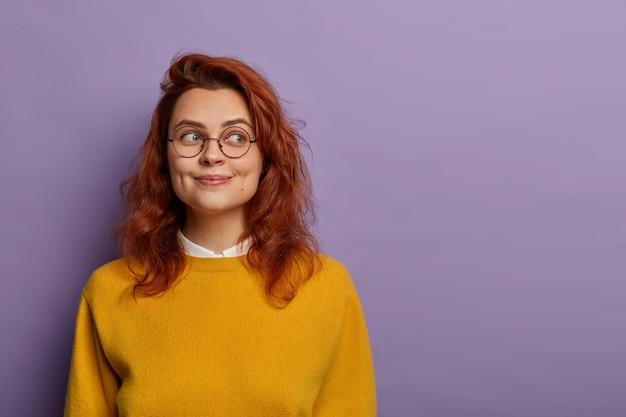 Colpo isolato di attraente donna rossa ha un'espressione del viso sognante, guarda da parte, indossa occhiali da vista e maglione giallo