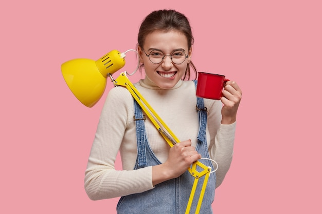 Isolated shot of attractive smiling woman bites lower lip, wears round glasses, denim overalls, has fun during coffee break, carries lamp