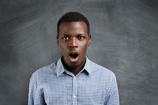 Colpo isolato di attraente giovane cliente africano con stupore e piena incredulità, mentre è sorpreso da alcune notizie inaspettate o da grandi prezzi di vendita, aprendo ampiamente la bocca