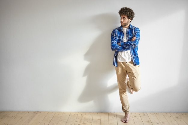 Isolated shot of attractive young caucasian man with thick beard and bare feet posing indoors standing against white blank wall  with copy space for your promotional content