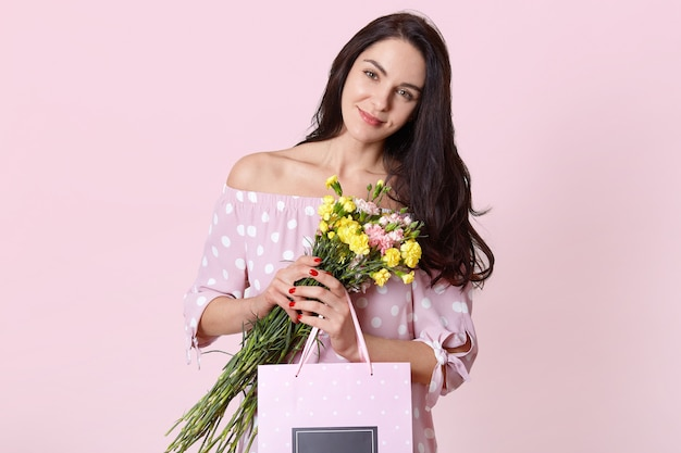 Isolated shot of attractive young european woman has black long hair, wears polka dot dress, holds gift bag and flowers, poses on light pink wall, celebrates international womens day