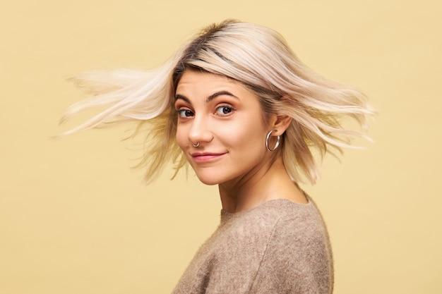 Colpo isolato di bella donna giovane incredibile in elegante maglione oversize girando con i capelli biondi che scorre nel vento