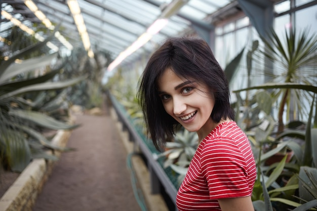Isolated shot of beautiful charismatic young brunette woman in her twenties smiling cheerfully at camera while walking in plant nursery among various tropical trees and shrubs, feeling carefree