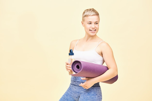 Colpo isolato di bella felice giovane istruttrice femminile con capelli tinti di folletto andando per allenamento portando una bottiglia di vetro non usa e getta con acqua e stuoia di yoga arrotolata, distogliendo lo sguardo con un ampio sorriso