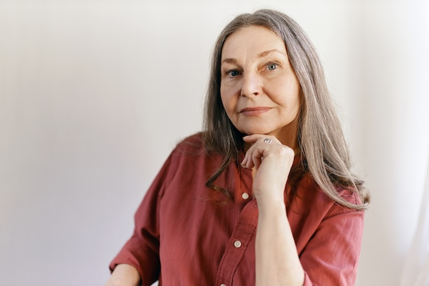 Isolated shot of beautiful thoughtful caucasian senior female with long gray hair posing at blank wall with copy space for your content, holding hand under chin, having pensive facial expression