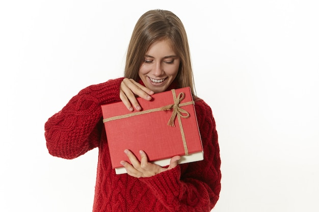Isolated shot of beautiful young lady in stylish spectacles and maroon pullover holding open box with birthday present, having sad disappointed facial expression, does not like what is inside