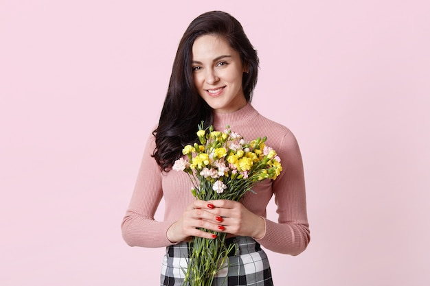 Isolated shot of charming cute dark haired woman wears rosy shirt, black and white checked skirt , holds bouquet of beautiful flowers